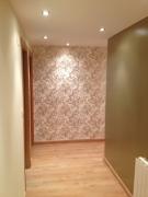 Отделка квартир под ключ. Прихожая после ремонта. Обои с золотым рисунком и покрашенная стена хорошо гармонируют друг с другом.