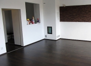 Ремонт домов квартир. Комната после перепланировки. Вместо двери сделана ниша. На пол уложен ламинат. Стену украшает декоративный щит.